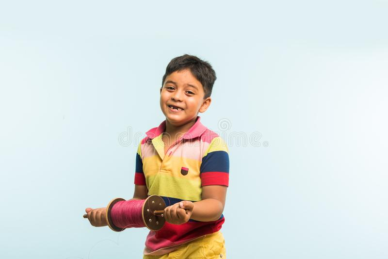 Indian small kid or boy holding spindal or chakri on Makar Sankranti festival, ready to fly Kite. Kite or Patang flying in India, cute and happy little indian royalty free stock photo