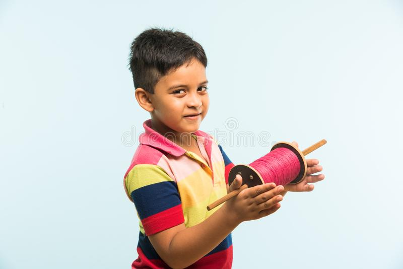Indian small kid or boy holding spindal or chakri on Makar Sankranti festival, ready to fly Kite. Kite or Patang flying in India, cute and happy little indian stock photos