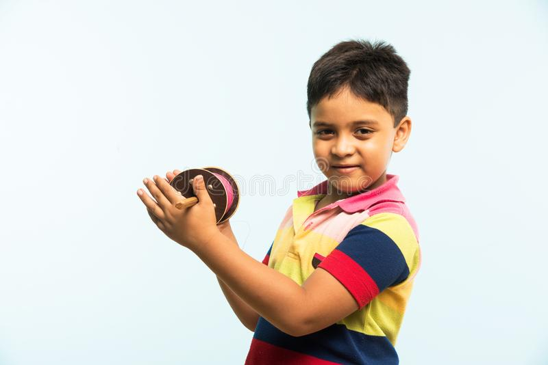 Indian small kid or boy holding spindal or chakri on Makar Sankranti festival, ready to fly Kite. Kite or Patang flying in India, cute and happy little indian stock image