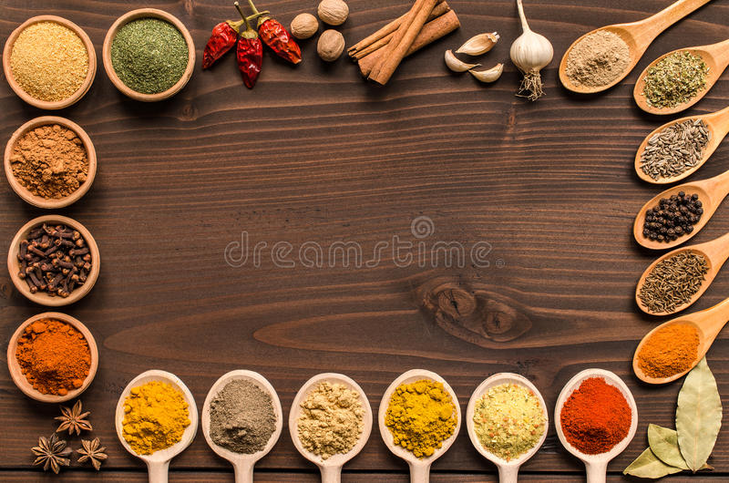Indian spices and dried herbs background - Top view. Frame of indian spices and dried herbs in bowls and wooden spoons - Top view royalty free stock photos