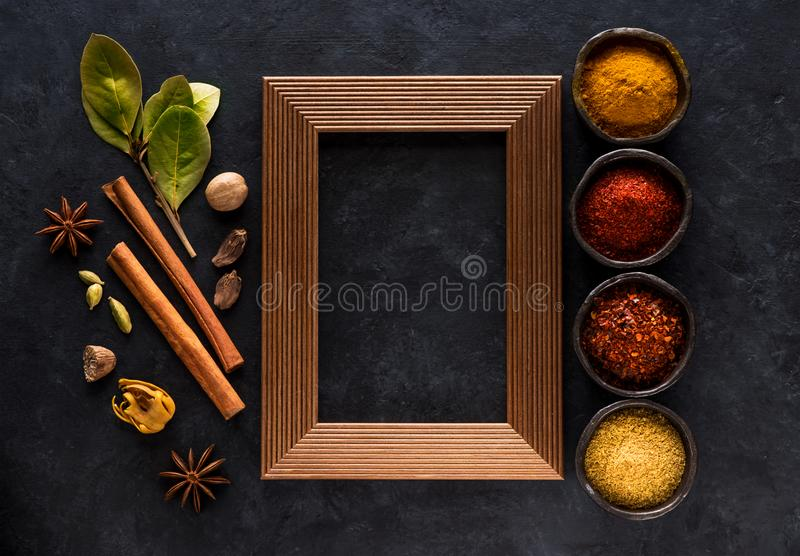 Indian spices, spicy and seasoning in bowls and empty wooden frame for text on black concrete background, stock photo