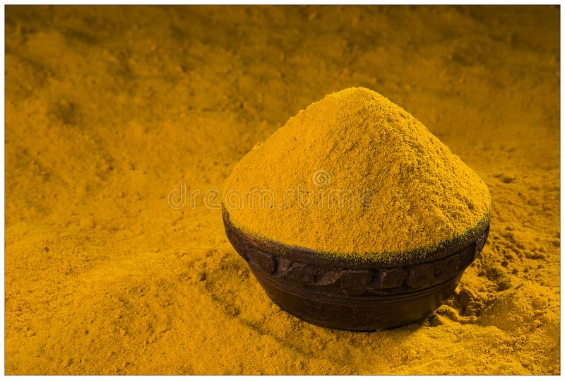 TURMERIC SPICES POWDER GRIND FLAVOUR. INDIAN SPICES TURMERIC POWDER GRIND BOWL nWOODEN YELLOW FLAVOUR HALDI royalty free stock photography