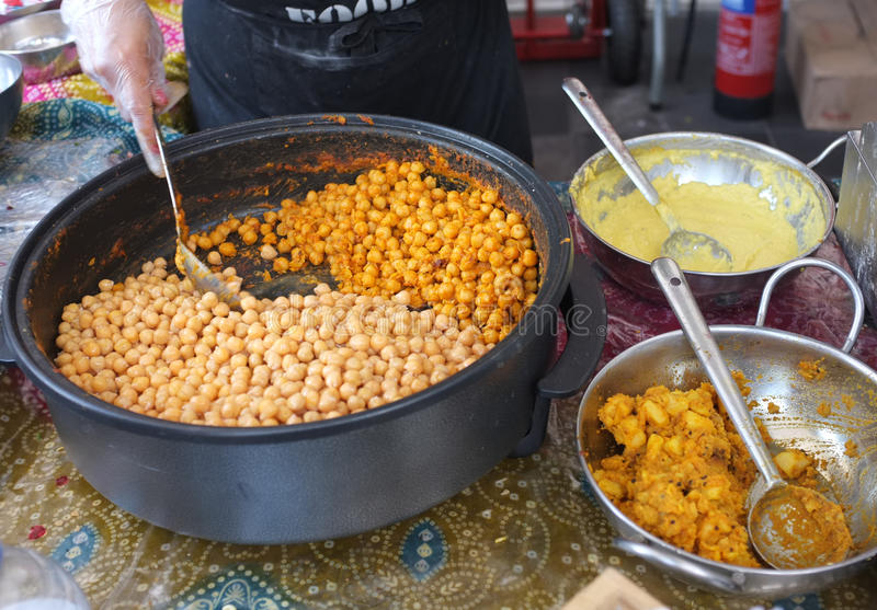 Indian Street Food. Being cooked and served at a market stall. Chana spicy chick peas, Lentil mixture for Dhosa and Bombay Potato with lady's hand and spoon royalty free stock photo