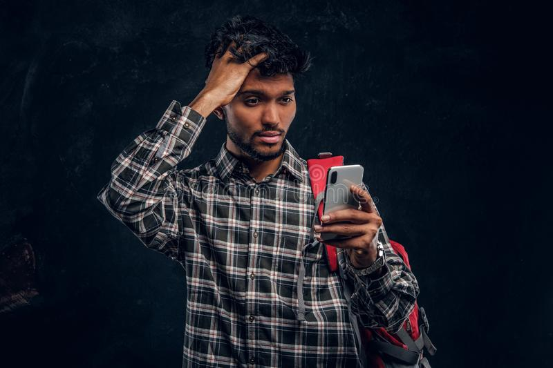 Indian student with a backpack forgot about something very important and with a frustrated look looks at his smartphone. Studio photo against a dark textured royalty free stock images