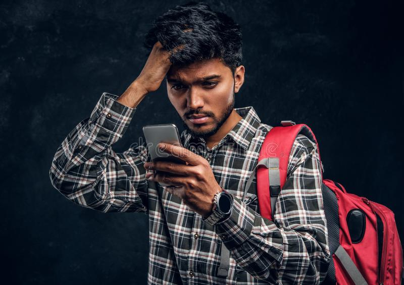 Indian student with a backpack forgot about something very important and with a frustrated look looks at his smartphone. Studio photo against a dark textured stock photography