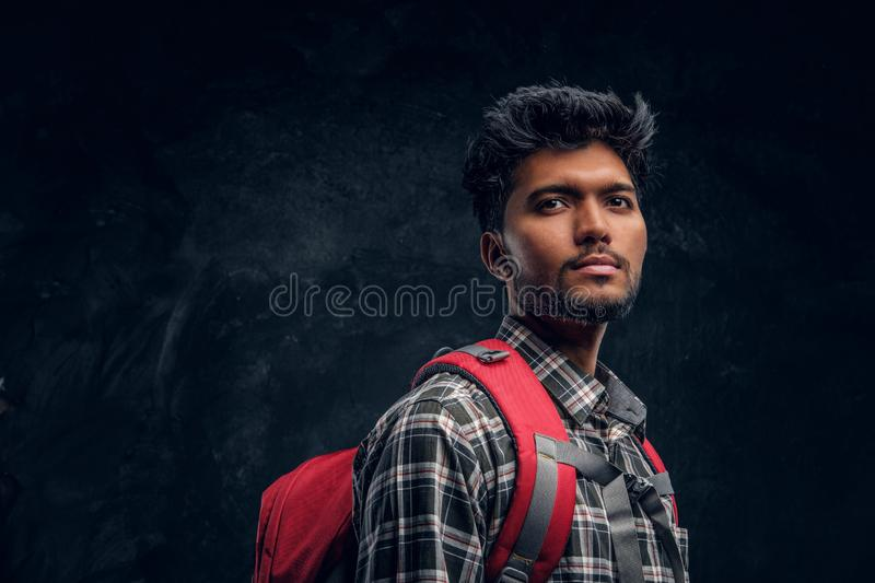 Indian student with a backpack wearing a plaid shirt. Studio photo against a dark textured wall. Portrait of a handsome Indian student with a backpack wearing a stock image