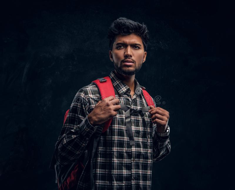Indian student with a backpack wearing a plaid shirt. Studio photo against a dark textured wall. Portrait of a handsome Indian student with a backpack wearing a royalty free stock photography