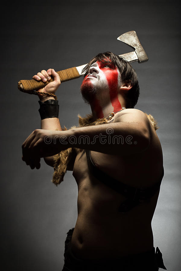 Indian. Studio portrait of man in war paint, with an ax in his hand, a warrior brandishing an ax up furiously, indian royalty free stock photos