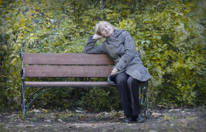 Indian summer. An elderly lady resting in a park on a bench in a warm autumn afternoon royalty free stock images