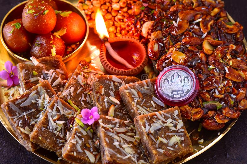 Diwali prasad thaali with earthen lamp diya and silver coin. Indian sweets like groundnut chikki brittle,dal chikki,mohanthaal or besan mithai chickpea flour royalty free stock photos