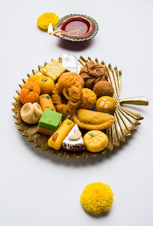 Indian sweets or Mithai for diwali festival with oil lamp or diya and gift box. Stock photo of Indian sweet or mithai and oil lamp or diya with gift box and royalty free stock photos