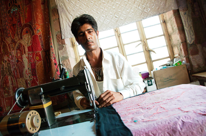 Indian tailor at work. An indian man is sewing a blanket using an old machine