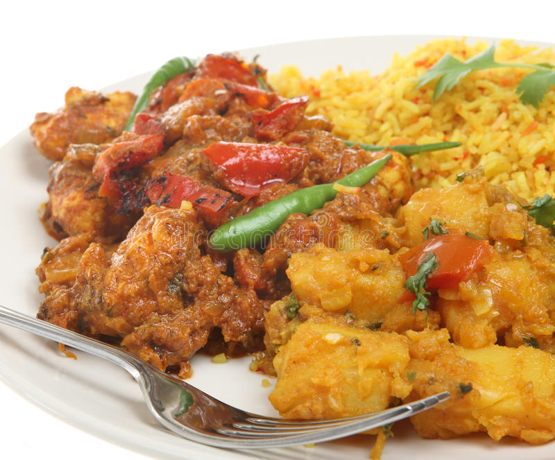 Indian Takeaway Curry Meal. Indian chicken jalfrezi with Bombay aloo potato curry and lemon rice royalty free stock photography