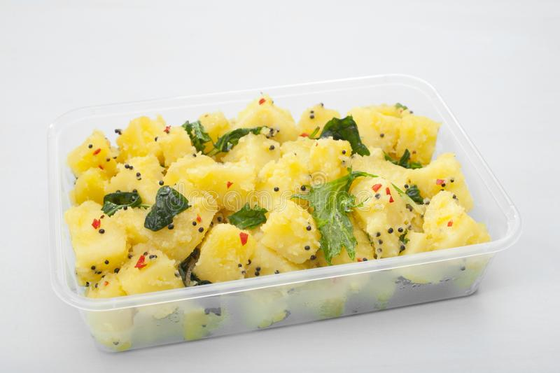 Indian Takeaway Food Aloo Saag Potato Spinach Curry Meal. A plastic takeaway container with popular Indian food aloo saag, potato and spinach curry royalty free stock photography