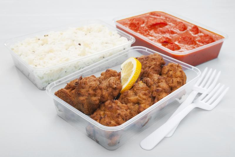 Indian Takeaway Food Selection Onion Bhaji Chicken Tikka Masala. A selection of popular Indian takeaway foods in plastic containers on a blue background, onion royalty free stock image