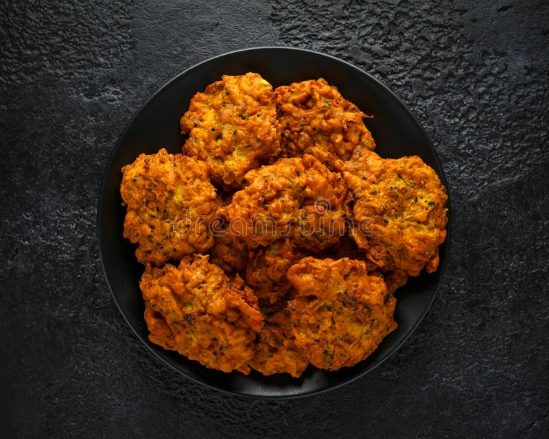 Indian takeaway food, spicy onion bhajis on black plate stock image