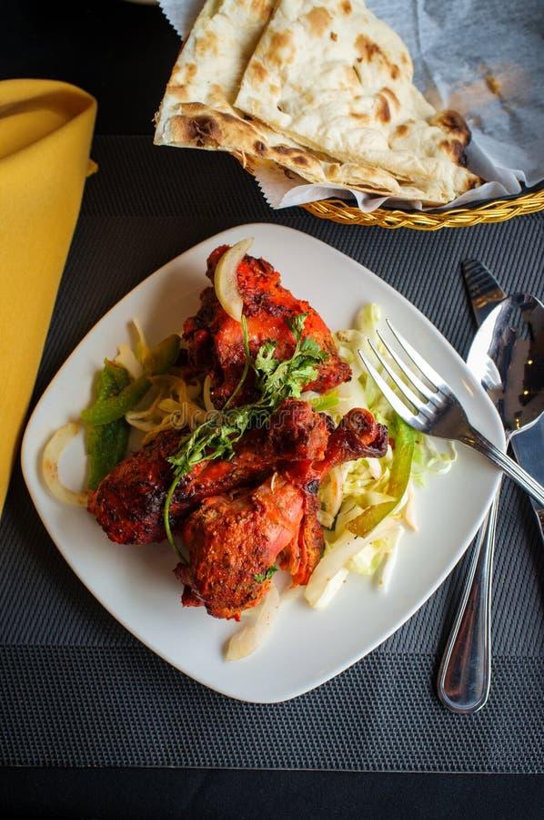 Indian Tandoori Chicken. Indian cuisine spicy Tandoori chicken with cilantro garnish royalty free stock images