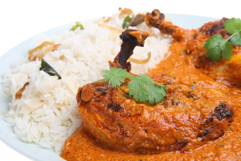 Indian Tandoori Chicken Curry. Chargrilled whole marinated chicken breasts in masala sauce with coconut rice royalty free stock photo