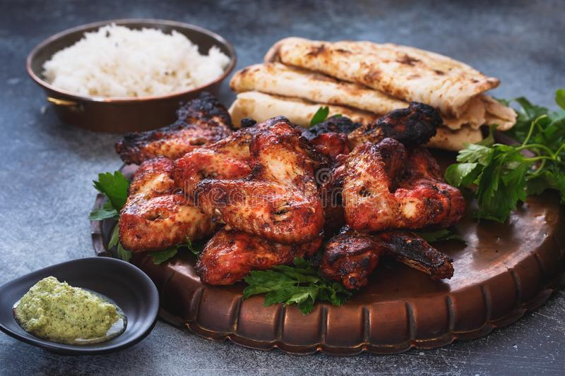 Indian tandoori chicken wings served with pilau rice and garlic naan. On rustic table , selective focus stock photography