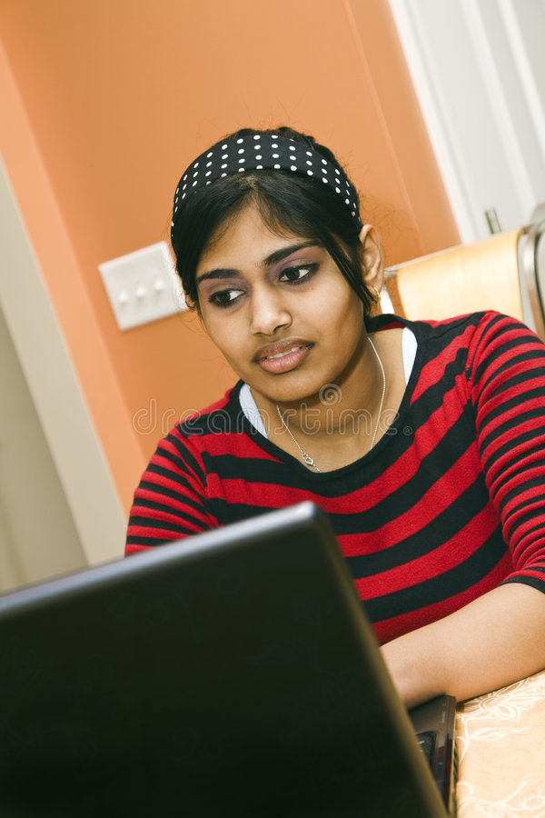 Indian Teen. Portrait of Indian teenager working with a laptop conputer royalty free stock images