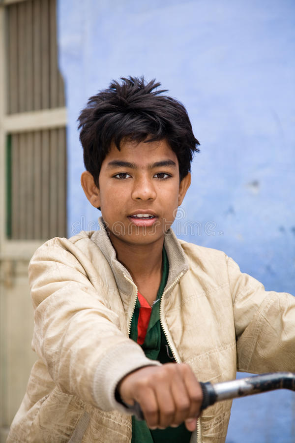 Indian teenager boy. Jodhpur, India - January 1, 2015 : An indian male teenager on his bike posing in the city of Jodhpur in central Rajasthan, India stock photography