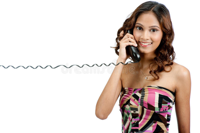Indian Teenager with Phone. A young and attractive indian teenager talking on the phone against white background stock photo