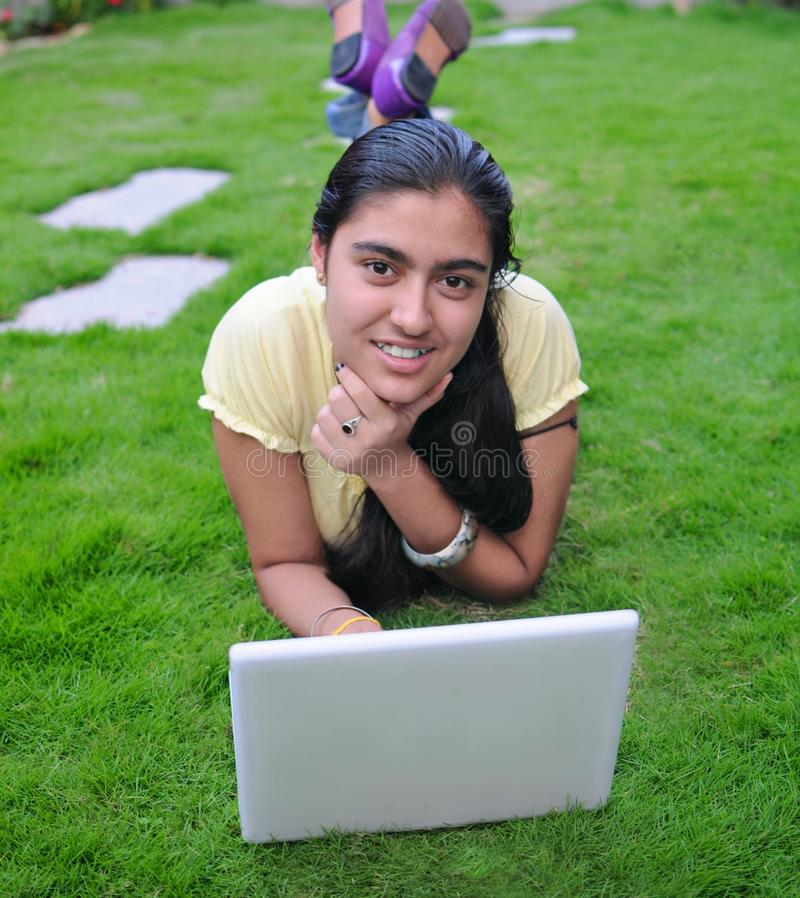 Indian teenager working on computer. Indian girl with a laptop, lying on green grass stock photo