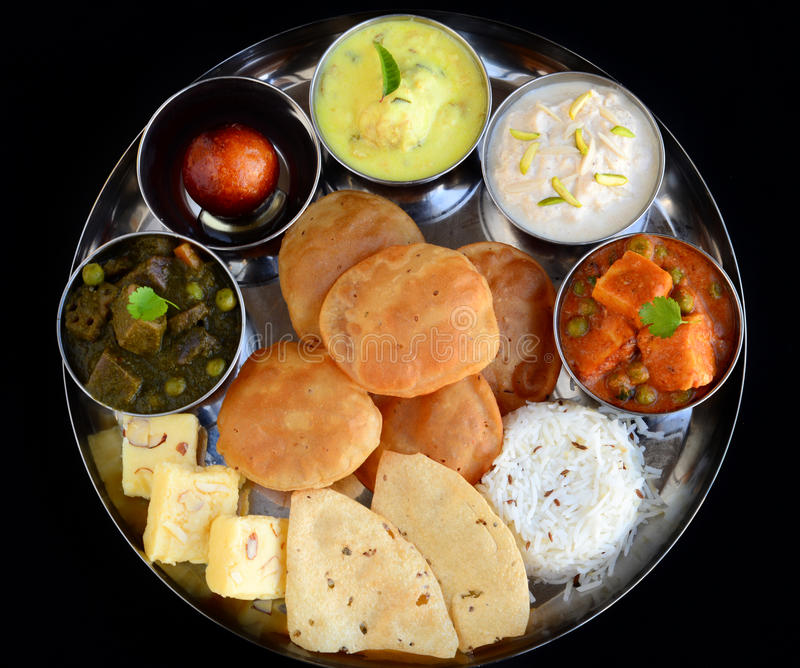Indian Thali or Indian meal. Indian meal (Thali) consisting of different curries,fried flat bread-poori,jeera rice,sweet like gulab jamun,mithai,kadhi ,matar stock photos