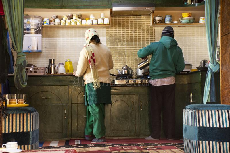 Indian or tibetan family cooking food for dinner in kitchen room of guest house of Leh Ladakh village at Himalayan valley stock photo