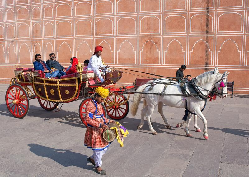 Indian tourists riding a horse cart in famous Jaipur City Palace, Rajasthan, India. JAIPUR, INDIA - JANUARY 4, 2019: Happy Indian tourists riding a horse cart in stock image