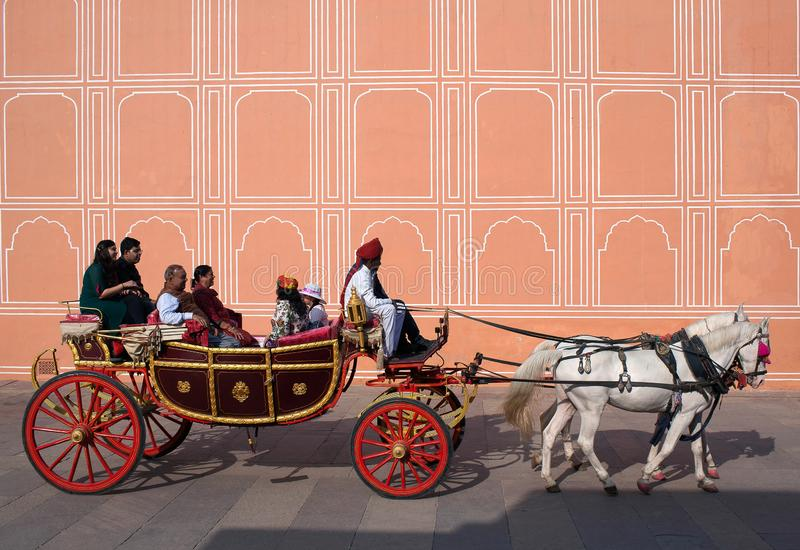 Indian tourists riding in a horse cart in Jaipur City Palace. JAIPUR, INDIA - JANUARY 4, 2019: Happy Indian tourists riding a horse cart in famous Jaipur City stock images