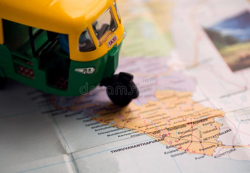 Indian toy rickshaw toy driving on Kerala map with Thiruvananthapuram city and others. Auto roads maps of old India. Indian toy rickshaw toy driving on Kerala royalty free stock image