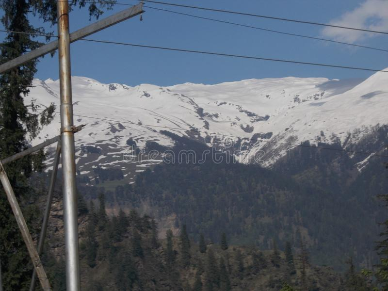 Indian travel site, Manali with ice, contains trees. Indian travel site, Manali with ice on its hilling area, in the year of 2014, with blue sky, contains lots stock photo