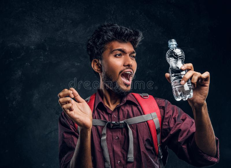 Indian traveler with a backpack got an incredible sensation drinking a sip of pure water from a mountain spring. Young Indian traveler with a backpack got an stock photos