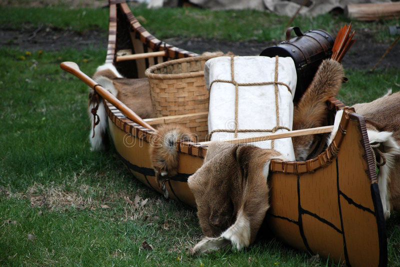 Indian canoe with furs and basket. Indian canoe filled with fur pelts and handmade basket for trade royalty free stock photo
