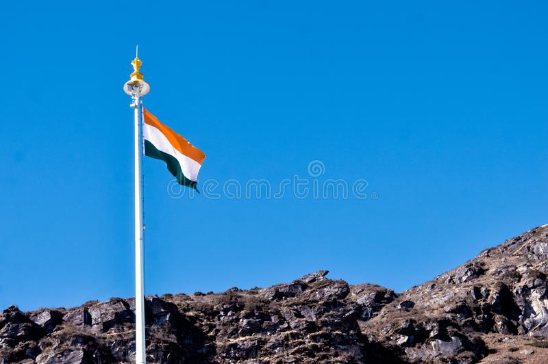 Indian tricolor national flag on a flagpole, waving in wind on mountain top. Blue sky background. Isilated Close up. 26 January royalty free stock photo
