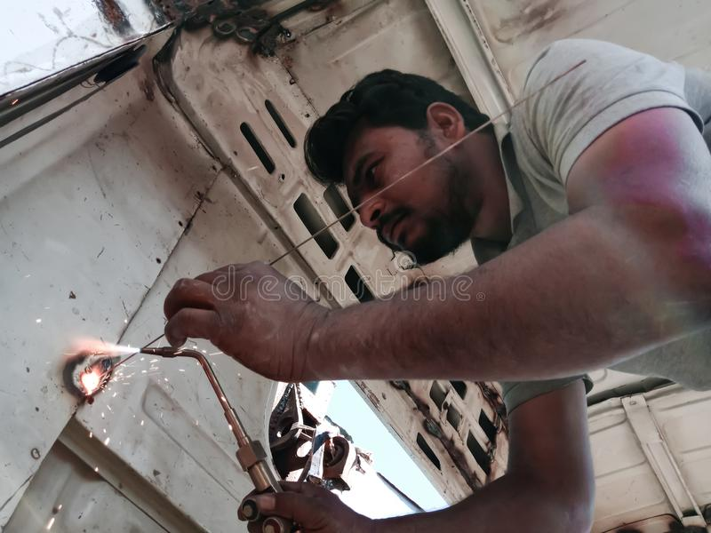An indian truck mechanic belding on the iron plate into the truck in India dec 2019 royalty free stock photos