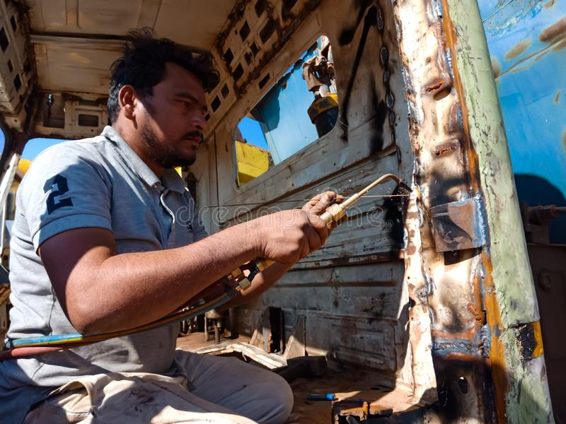 An indian truck mechanic belding on the iron plate into the truck in India dec 2019 stock image