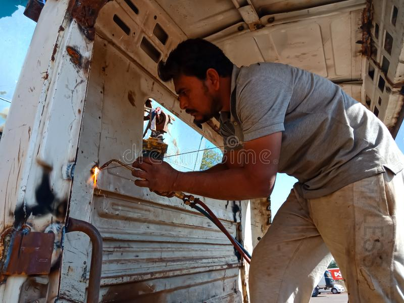 An indian truck mechanic belding on the iron plate into the truck in India dec 2019 stock photos