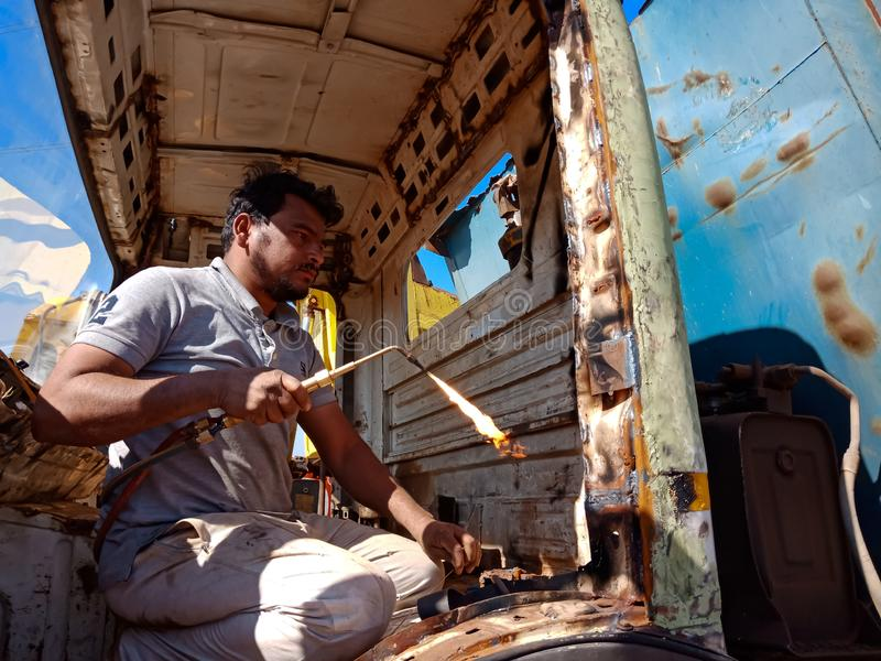An indian truck mechanic belding on the iron plate into the truck in India dec 2019 stock photo