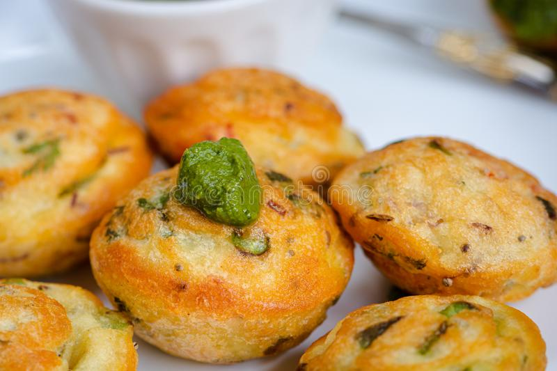 Indian vegan yellow lentil ball filled with fresh veggies and green chutney, appe in hindi. Indian vegan yellow lentil ball filled with fresh veggies such as stock photo