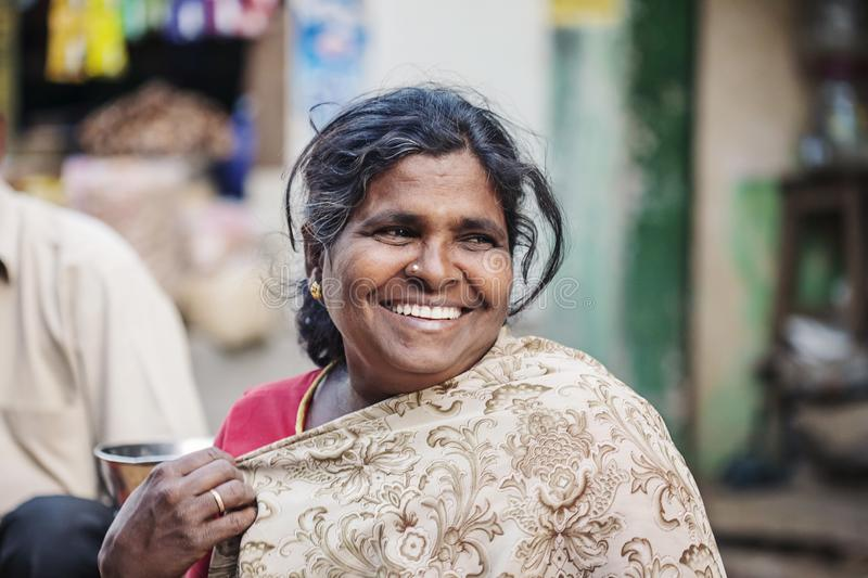 Indian vegetable outdoor street market female seller. Udaipur city in Rajasthan, India, January 2018: Indian vegetable outdoor street market female seller stock photo