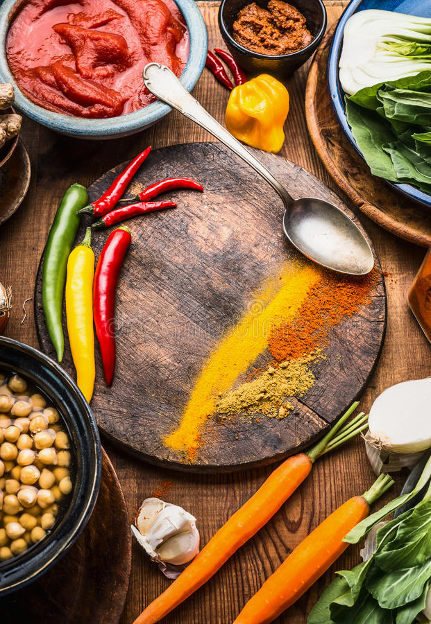 Indian vegetarian cooking ingredients with colorful ground spices , indian curry paste, chick peas , vegetables and spoon on wood. En background, top view, frame royalty free stock photo