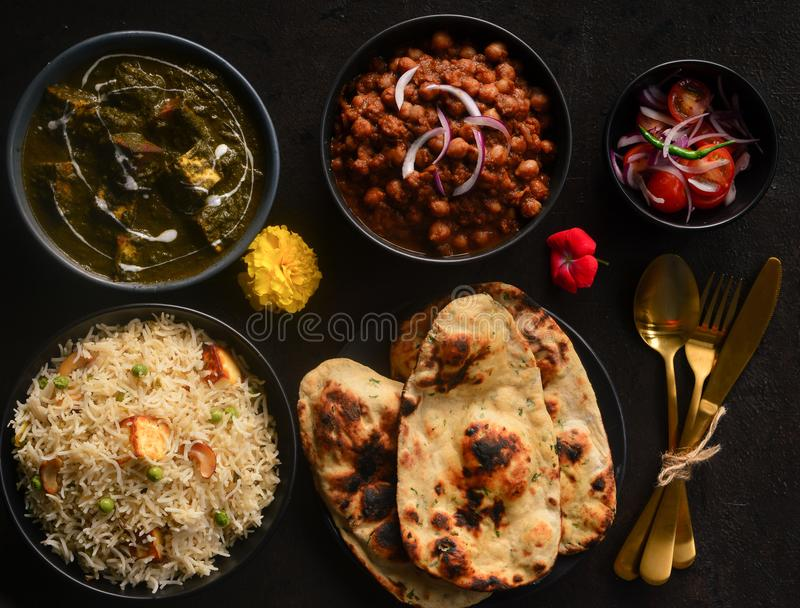Indian Vegetarian meal-punjabi veg platter. Indian vegeterian meal with palaki paneer,pindi chana ,vegetarian kashmiri pulao,Tandoori Roti and salad royalty free stock photo