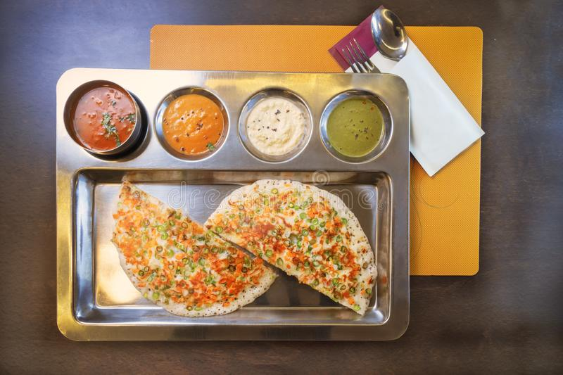 Indian vegetarian pancake. Served with mango juice on a steal plate and several type of sauce royalty free stock images