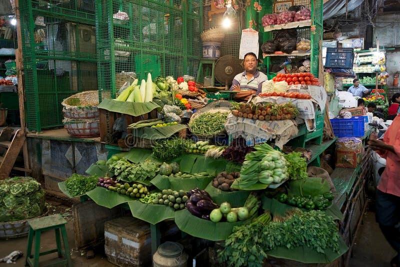 Indian vendor at the New Market, Kolkata, India. Indian vendor is selling vegetables at the New Market, Kolkata, india. New Market is an enclosed market located royalty free stock photos