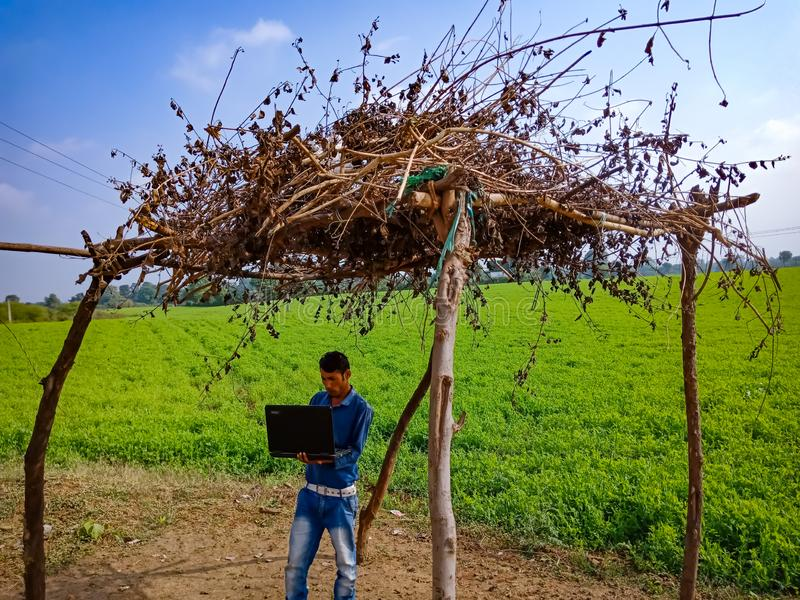 An indian village boy operating laptop into the hut at green field area in India January 2020 royalty free stock photography