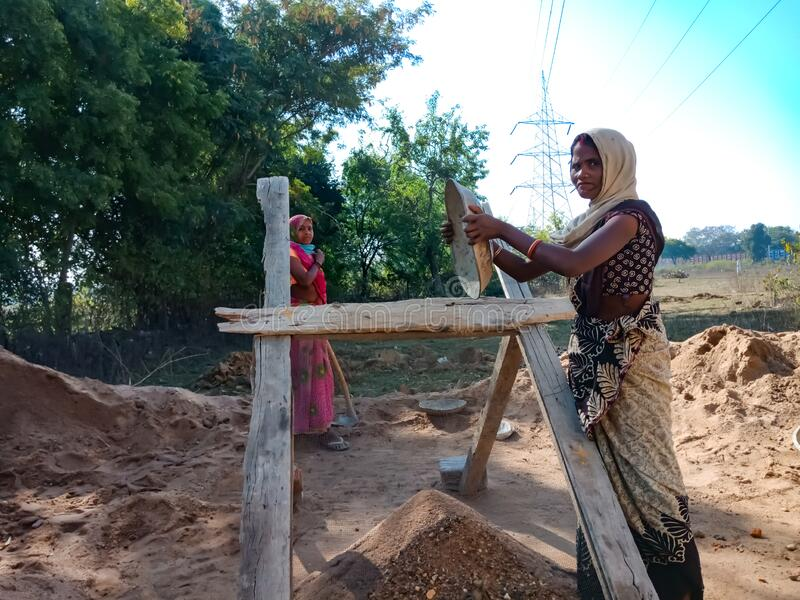 indian village female labour holded sand pot during filtration on construction site in India January 2020 royalty free stock image