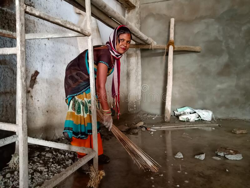 an indian village lady labour cleaning floor at construction site in India January 2020 royalty free stock image