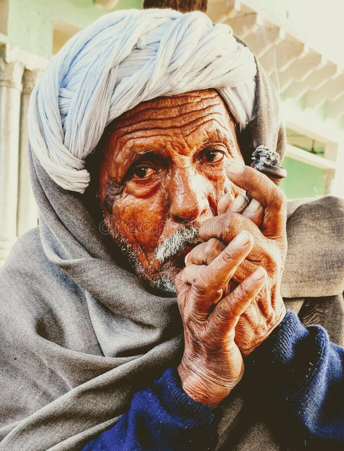Indian village old man smoking Ganja Marihuana with chillum/hukkah in Rajasthan's traditional dress turban on head in winter royalty free stock photo